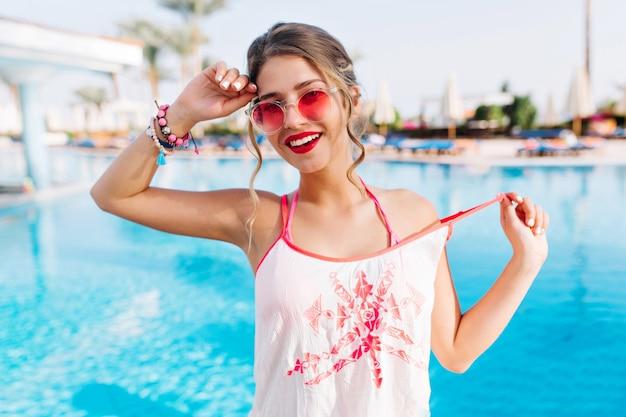 Nahaufnahmeporträt des gut aussehenden gebräunten mädchens in der rosa sonnenbrille, die mit den händen oben und im glücklichen gesichtsausdruck aufwirft Kostenlose Fotos