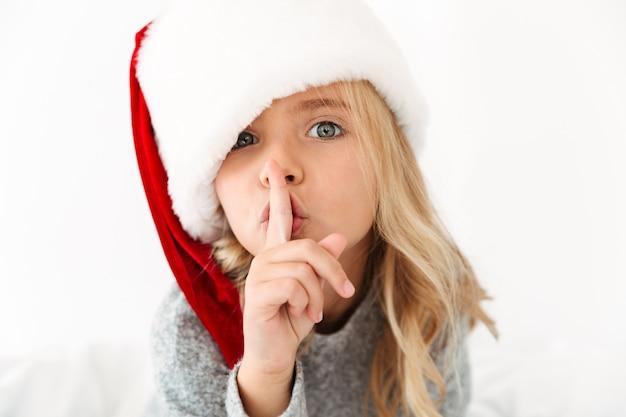Nahaufnahmeporträt des hübschen kleinen mädchens in der mütze des weihnachtsmanns, das schweigengeste zeigt, Kostenlose Fotos