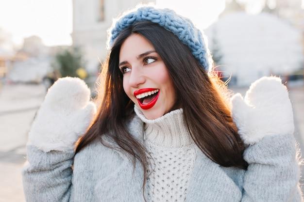 Nahaufnahmeporträt des hübschen mädchens mit dem schwarzen langen haar, das mit den händen oben im kalten tag aufwirft. foto im freien der niedlichen europäischen dame im blauen hut und in den weißen handschuhen, die winterwochenende genießen. Kostenlose Fotos