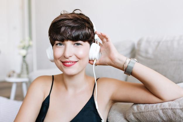 Nahaufnahmeporträt des leicht gebräunten lachenden mädchens mit grauen augen, die musik genießen Kostenlose Fotos