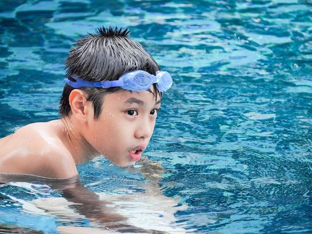 Nahaufnahmeporträt des netten jungen im swimmingpool Premium Fotos