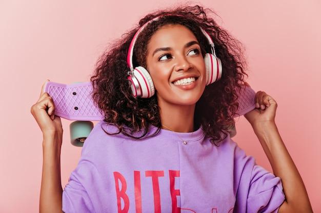 Nahaufnahmeporträt des positiven weiblichen modells im lila hemd, das oben mit lächeln schaut. schöne afrikanische junge dame, die lieblingslied in den kopfhörern hört. Kostenlose Fotos