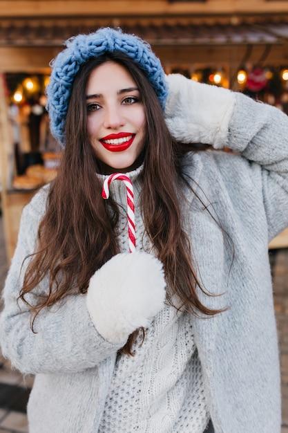Nahaufnahmeporträt des romantischen europäischen mädchens mit dunklem haar, das mit süßem weihnachtslutscher aufwirft. foto des hübschen kaukasischen weiblichen modells in den weißen handschuhen und im blauen hut, die spaß haben Kostenlose Fotos