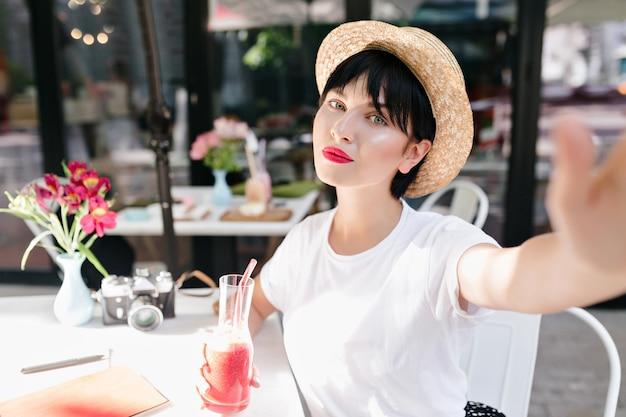 Nahaufnahmeporträt des romantischen mädchens mit blasser haut und dunklem haar, das im gemütlichen straßencafé mit blumen auf tisch kühlt Kostenlose Fotos