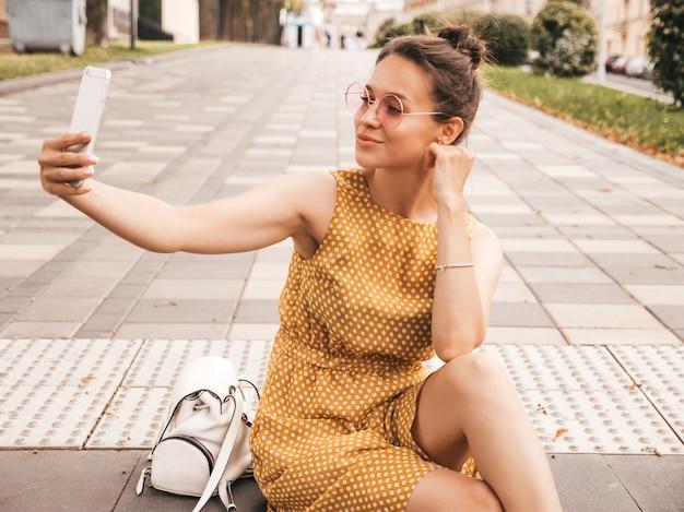 Nahaufnahmeporträt des schönen lächelnden brunettemädchens im sommerhippie-gelbkleid. vorbildliches nehmendes selfie auf smartphone frau, die fotos am warmen sonnigen tag in der straße in der sonnenbrille macht Kostenlose Fotos
