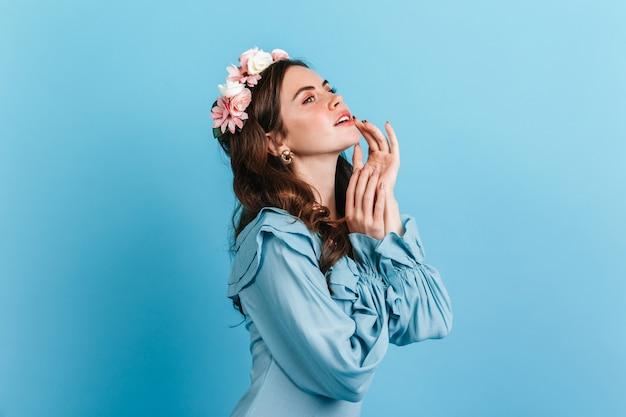 Nahaufnahmeporträt des sinnlichen mädchens in der seidenbluse mit rüschen. dame mit blumen im haar, das lippen berührt. Kostenlose Fotos