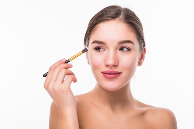 Nahaufnahmeporträt einer frau, die trockene kosmetische tongrundierung auf dem gesicht unter verwendung des make-up-pinsels lokalisiert auf weißer wand anwendet Kostenlose Fotos