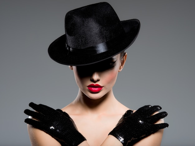 Nahaufnahmeporträt einer frau mit schwarzem hut und handschuhen mit roten lippen Kostenlose Fotos