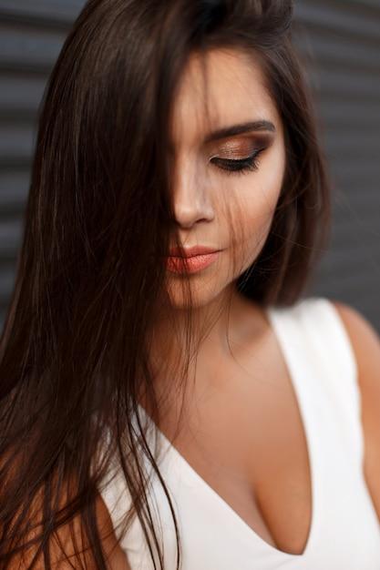 Nahaufnahmeporträt einer jungen schönen frau mit make-up im weißen kleid auf einem dunklen hintergrund Premium Fotos