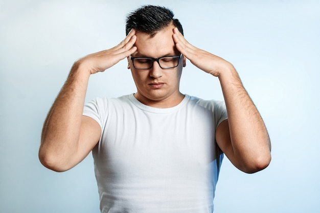 Nahaufnahmeporträt eines mannes, sein gesicht mit seinen händen bedeckend. Premium Fotos