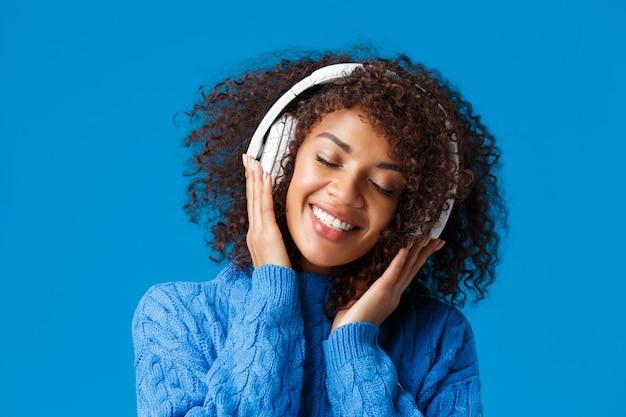 Nahaufnahmeporträt glücklich lächelnde, romantische und zarte afroamerikanerfrau, die musik in kopfhörern genießt, kippkopf schließen augen träumerisch und grinsend entzückt, blaue wand. Kostenlose Fotos