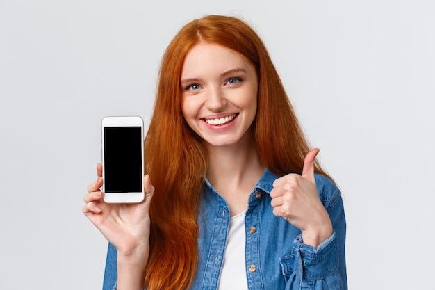 Nahaufnahmeporträt stellte die schöne rothaarigefrau zufrieden, die anwendung verwendet, empfehle, sie herunterzuladen, foto-app annoncierend, onlineshop, show-smartphoneanzeige und daumen-oben, wie Premium Fotos