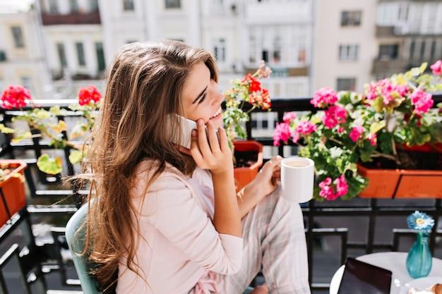 Nahaufnahmeporträt von der seite hübsches mädchen im pyjama, das frühstück auf balkon am sonnigen morgen hat. sie hält eine tasse in der hand und spricht lächelnd am telefon. Kostenlose Fotos
