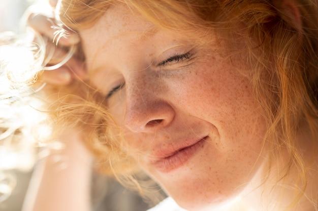 Nahaufnahmerothaarigefrau mit geschlossenen augen Kostenlose Fotos