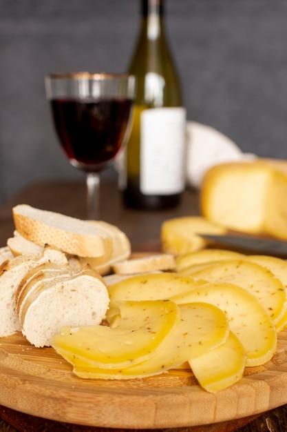 Nahaufnahmescheiben käse mit einem glas wein Kostenlose Fotos