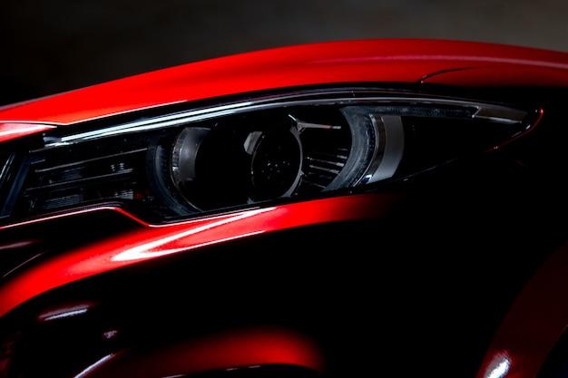 Nahaufnahmescheinwerfer des glänzenden roten luxus-suv-kleinwagens. elegante elektroauto-technologie Premium Fotos