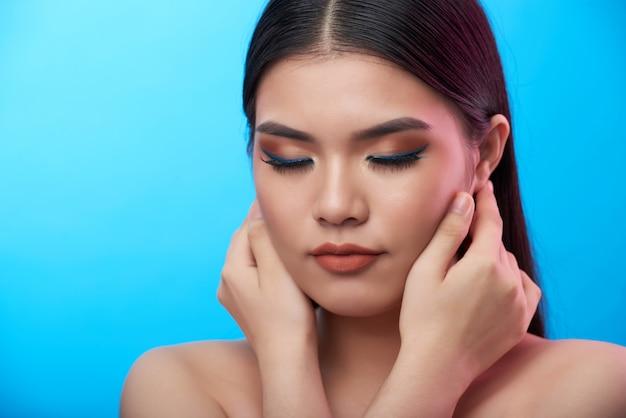 Nahaufnahmeschuß der jungen asiatin mit dem make-up, das mit den geschlossenen augen und händen berühren backen aufwirft Kostenlose Fotos