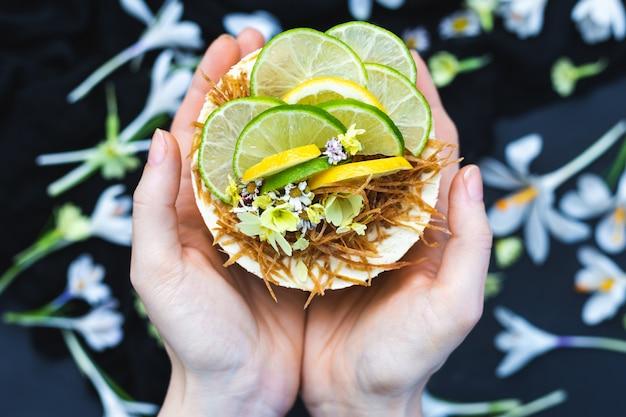 Nahaufnahmeschuss der weiblichen hände, die einen rohen veganen kuchen halten Kostenlose Fotos