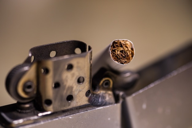 Nahaufnahmeschuss einer zigarette in einem zippofeuerzeug Kostenlose Fotos