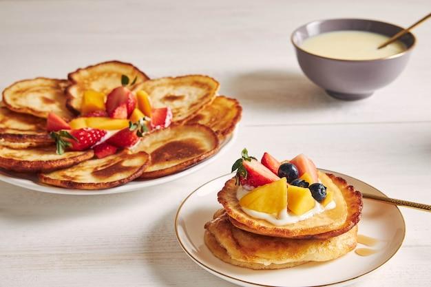 Nahaufnahmeschuss von köstlichen pfannkuchen mit früchten auf der oberseite Kostenlose Fotos