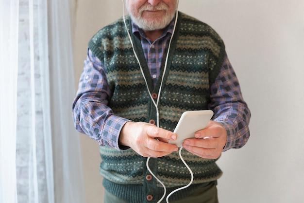 Nahaufnahmesenior, der musik auf mobile spielt Kostenlose Fotos