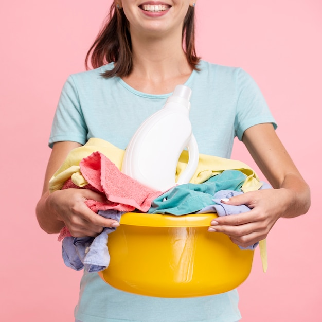 Nahaufnahmesmileyfrau, die einen wäschekorb hält Kostenlose Fotos