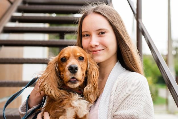 Nahaufnahmesmileyfrau, die ihren hund hält Kostenlose Fotos