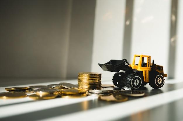 Nahaufnahmestapel prägt mit dem gelben traktor, der als geschäft und industrielles konzept verwendet Premium Fotos
