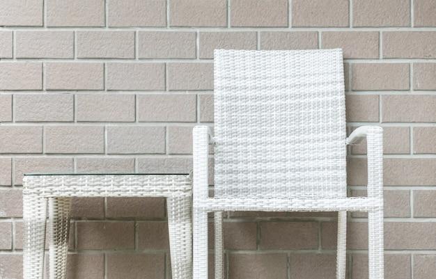 Nahaufnahmetabelle und -stuhl auf backsteinmauerbeschaffenheitshintergrund Premium Fotos