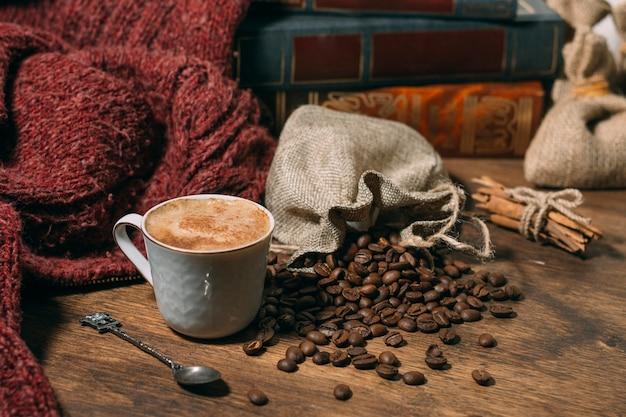 Nahaufnahmetasse kaffee mit gebratenen bohnen Kostenlose Fotos