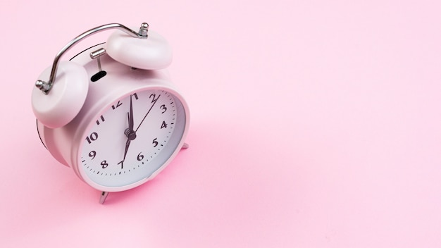 Nahaufnahmeuhr mit rosa hintergrund Kostenlose Fotos