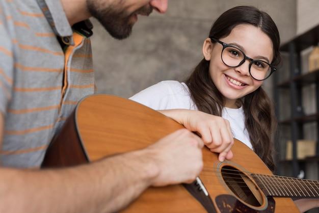 Nahaufnahmevater, der mädchen lehrt, gitarre zu spielen Kostenlose Fotos