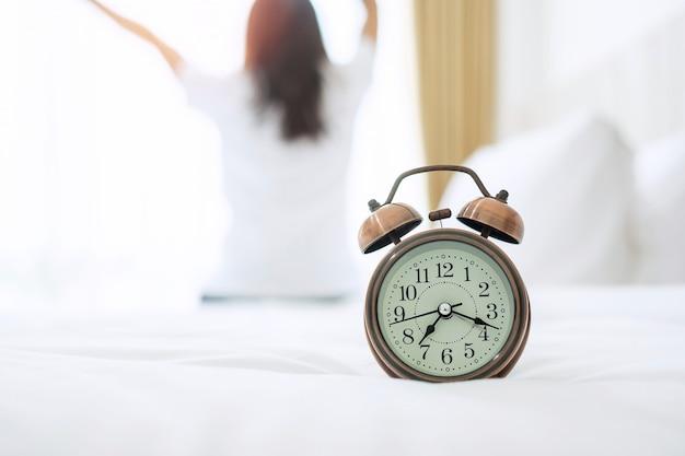 Nahaufnahmewecker im bett mit der glücklichen frau, die sich nach dem aufwachen ausdehnt Premium Fotos