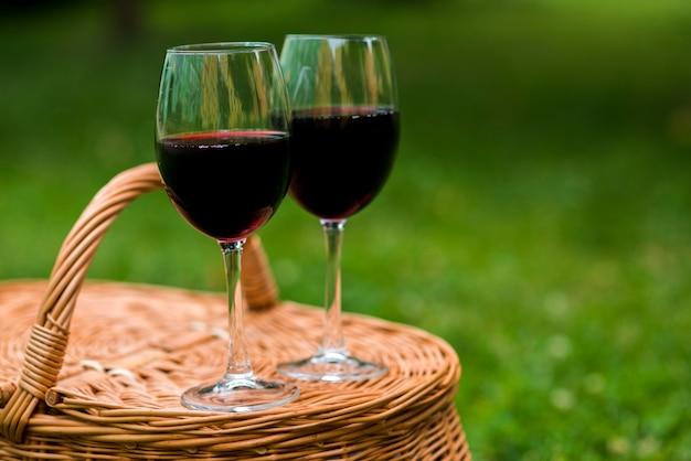 Nahaufnahmeweingläser auf einem picknickkorb Kostenlose Fotos