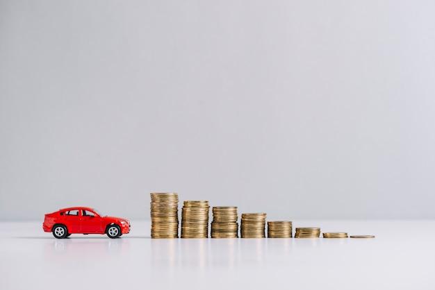 Nahe abnehmende gestapelte münzen des roten autos Kostenlose Fotos