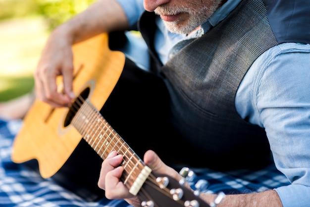 Nahe ansicht starker mann, der gitarre spielt Kostenlose Fotos