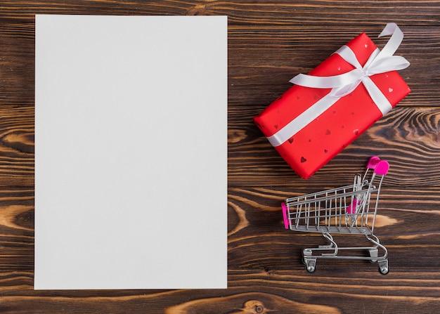 Nahe rotem präsentkartonpapier mit weißem band und einkaufslaufkatze Kostenlose Fotos