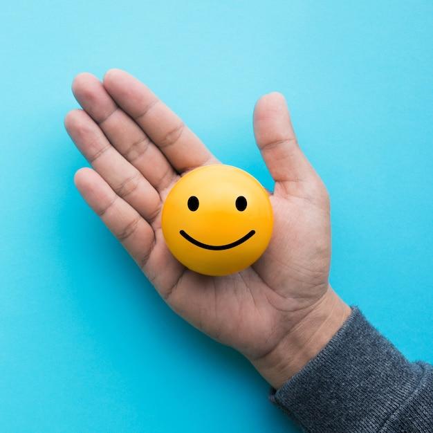 Nahkampfhand, die gelben emoticonball auf blauem farbhintergrund hält Premium Fotos