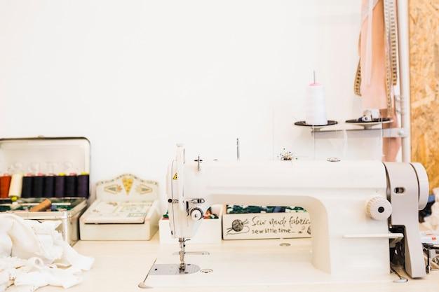 Nähmaschine und Gewebeausrüstungen auf Werkbank   Download der ...