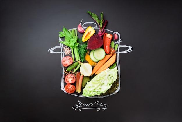 Nahrungsmittelbestandteile für das mischen der sahnigen suppe auf gemalter kochtopf über schwarzer tafel. Premium Fotos