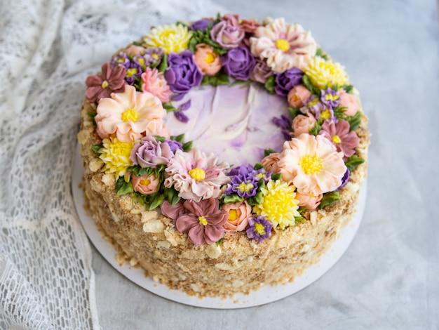 Napoleon-torte mit vanillecreme, dekoriert mit buttercreme-blüten Premium Fotos