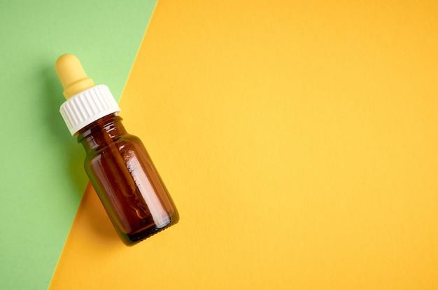 Nasentropfen-flaschenzusammensetzung, glasflasche auf gelbem und grünem hintergrund mit copyspace Premium Fotos