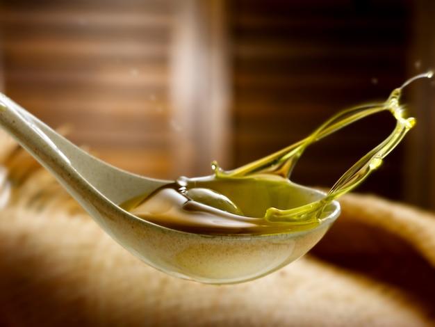 Natives olivenöl extra mit oliven in einem löffel Premium Fotos