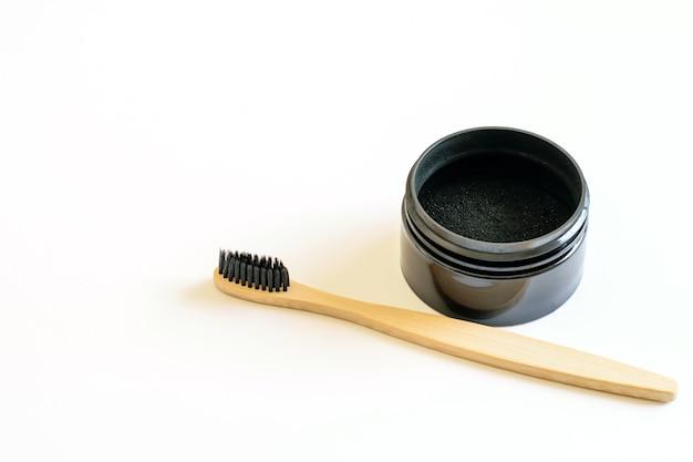 Natürliche aktivkohle- und bambuszahnbürste zur zahnaufhellung auf weiß Premium Fotos