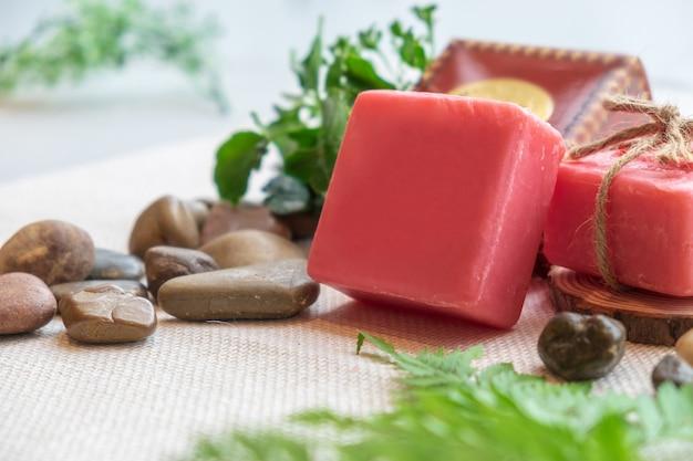 Natürliche handgemachte rote farbe der kräuterseife mit naturblattstein auf brauner stoffsonnenbeleuchtung Premium Fotos