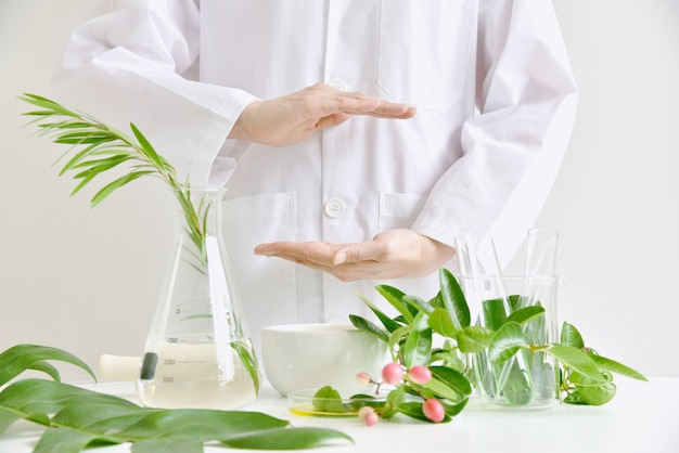 Natürliche hautpflege-schönheitsproduktforschung, entdeckung grüner organischer kräuteressenzen im wissenschaftslabor, dermatologe-handpräsentationsprodukt für das branding. Premium Fotos