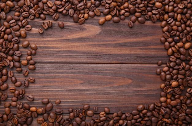 Natürliche kaffeebohnen auf braunem hölzernem hintergrund Premium Fotos