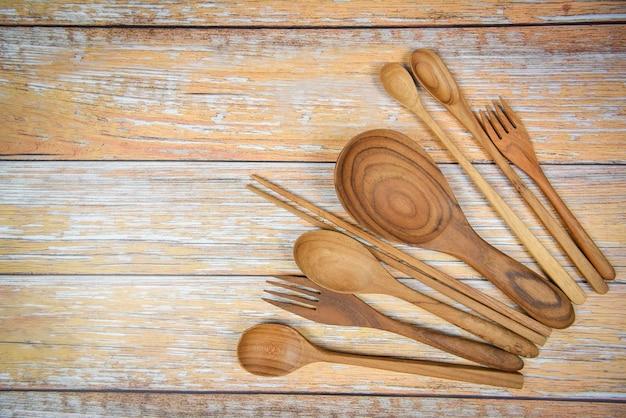 Natürliche küche bearbeitet den hölzernen produkt- / küchengeräthintergrund mit löffelgabelessstäbchenschöpflöffel und nachtischlöffel verschiedene größen auf dem hölzernen plattengegenstandgerät Premium Fotos