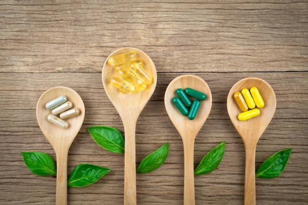 Natürliche nahrungsergänzungsmittel in kapseln aus kräutern auf holz Premium Fotos