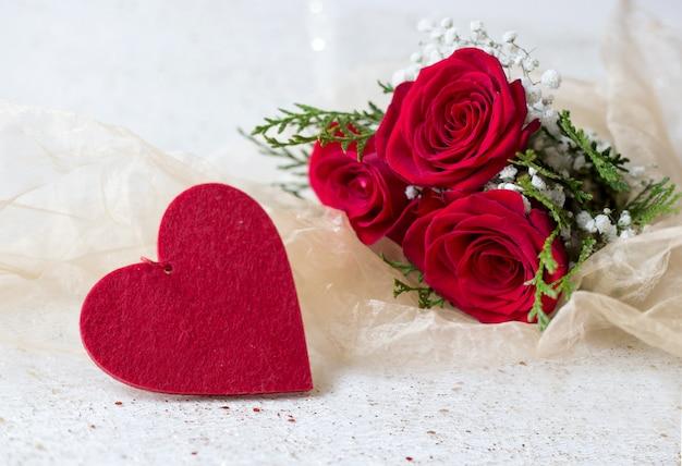Natürliche rote rosen und filzherz mit liebesgrußkarte mit goldenem sparkly hintergrund Premium Fotos